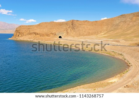 picturesque scenery in blue and sandy shades, way out of tunnel, dirt road and highway along the deserted shore of a high mountain lake Pangong Tso, ripples on a water surface, Tibet