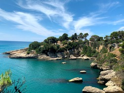 Picturesque sea Adriatic coast of Montenegro. View on cape Jadran. Turquoise Mediteran sea and rocky shore with evergreen coniferous trees. Beautiful clouds in blue sky. Wonderful summer landscape