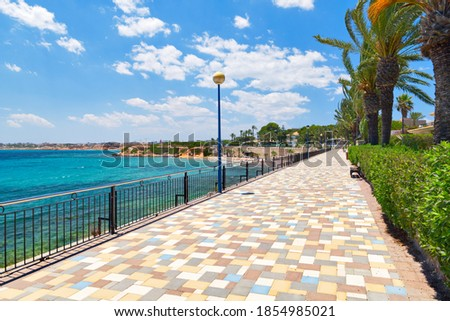 Picturesque seafront promenade of Punta Prima. Empty fenced  pedestrian walkway and turquoise Mediterranean Sea. Costa Blanca, Spain. Summer vacation, travel and holidays concept Stockfoto ©