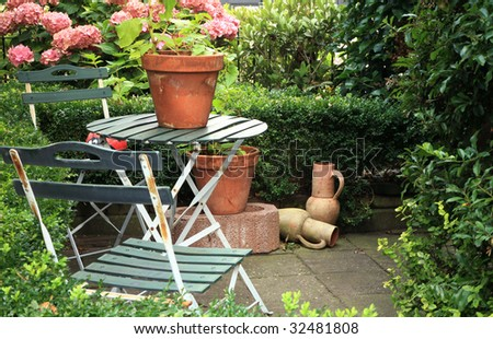 Picturesque small garden in backstreet in Netherlands with hydrangea , jugs, table and chairs and hedge.
