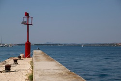 Picturesque stone peer with red steel signal post that aids safe navigation trough shallow waters and easy access to Krapanj harbour on a sunny summer day