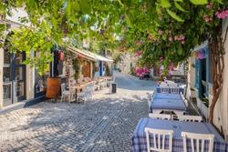Picturesque street in Mediterranean Alacati Town in Turkey. Alacati is popular historical tourists destination in Turkey. Cozy outdoor cafe and restaurants