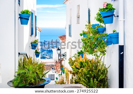 Picturesque street of Mijas with flower pots in facades. Andalusian white village. Costa del Sol. Southern Spain #274925522