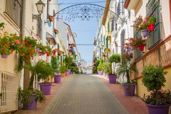 Picturesque street with flowers on sunny day. Old town of Estepona, Spain.