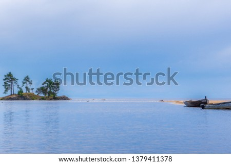 Picturesque summer landscape in minimal style with mouth of northern river flowing into lake in cloudy day. Travelling and discovering distant places of Earth. View from water. Karelia, Russia #1379411378
