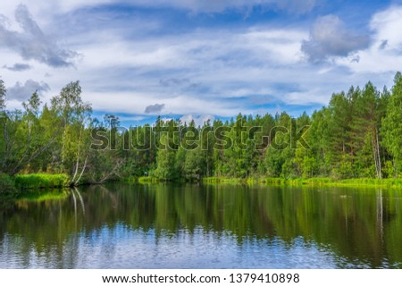 Picturesque summer landscape with northern river and forest in summer cloudy day. Travelling and discovering distant places of Earth. View from floating boat. Chernaya river, Karelia, Russia #1379410898