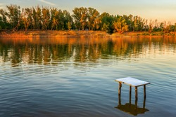 Picturesque summer landscape with riverbank at sunset. Calm plain river, empty table in water. Wonderful nature, beautiful natural background. Akhtuba river, Astrakhan region, Russia