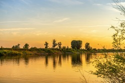 Picturesque summer landscape with riverbank at sunset. Calm plain river, reflection in water. Wonderful nature, beautiful natural background. Akhtuba river, Astrakhan region, Russia