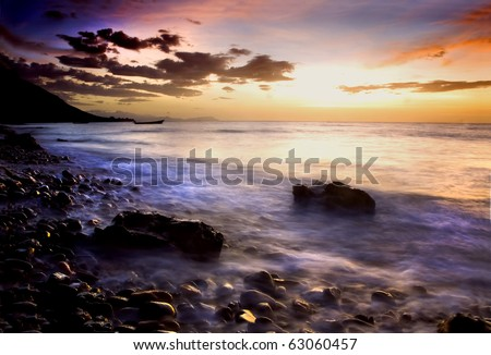 Picturesque sunset and cloudscape over rocky coastline with silhouetted boat in background, Socotra or Soqotra island in Indian ocean.