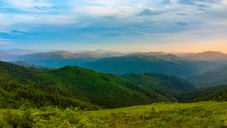 Picturesque sunset in the mountains. A calm evening fell on mountain ranges overgrown with green forest. The sky is painted with the warm colors of the setting sun