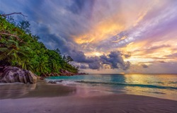 Picturesque sunset on dream beach at anse georgette on praslin on the seychelles. A big granite rock, turquoise water, palm trees and a romantic sky...