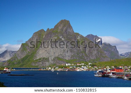 Picturesque town of Reine by the fjord on Lofoten islands in Norway with high mountain peaks towering above