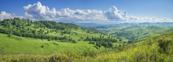Picturesque valley, panoramic mountain view. Bright sunlight, spring greens of forests and meadows.
