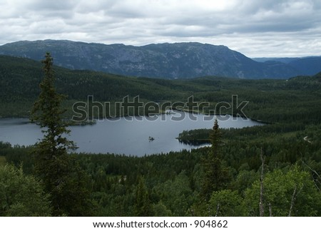 Picturesque view at Norwegian lake in the mountain forest under cloudy skies. - stock photo