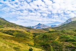 Picturesque view of Pyrenees landscape with green meadows and mountains in daytime. Summer vacation trip in the mountain, in the Val D'aran, Aran Valley, Pyrenees, Catalonia, Spain.