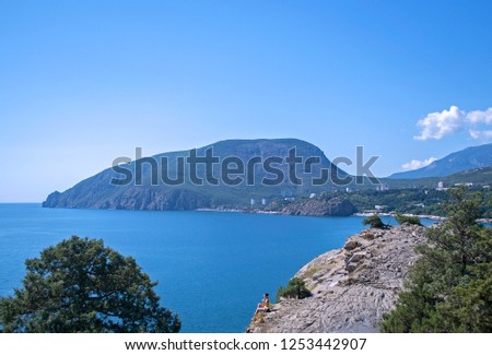 Picturesque view of sea bay surrounded with mountains & rocks. Young woman sitting on rock & looking to sea. Ayu-Dag, famous mountain, symbol of Crimea