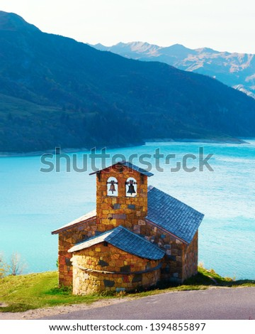 Picturesque view of stone chapel on Roselend lake coast (Lac de Roselend) in France Alps (Auvergne-Rhone-Alpes). Landscape photography #1394855897