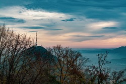 Picturesque view of telecommunication tower in dark sunset sky over the mountains. Silhouette of radio communication tower. Enchanted nature landscape. Orange and blue sky theme. Isolated antenna.