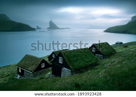 Picturesque view of tradicional faroese grass-covered houses in the village Bour. Drangarnir and Tindholmur sea stacks on background. Vagar island, Faroe Islands, Denmark. Landscape photography Foto stock ©