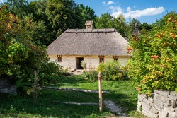 Picturesque view of Ukrainian house with hay roof. Old Ukrainian straw thatched country cottage.