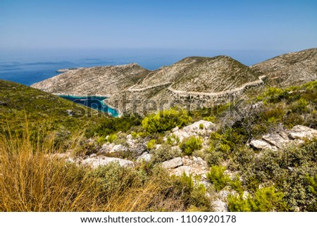Stock Photo Picturesque view of valley with mountain winding road up to a small port with boats. Colorful vacation seascape of blue sea and green hills.