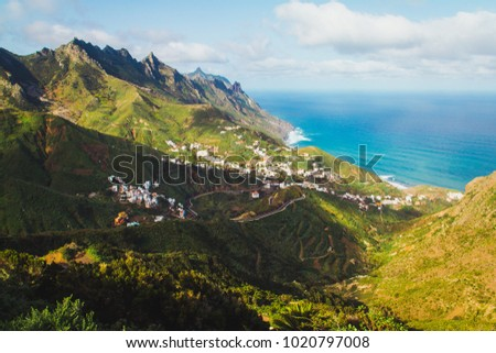 Stock Photo Picturesque view of village place in green valley in mountains with view of ocean on background.