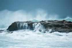 Picturesque view of wild waves tilting against rock in ocean.