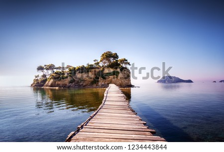Picturesque view on lonely island Cameo in Greece, part of island Zakynthos or Zante, Port Sostis. Dramatic scenery of solitude island in ocean with wooden path. Iconic landmark on Zakinthos island.