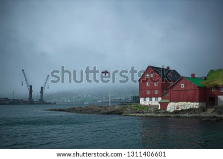 Picturesque view to the Skansapakkhusið the seat of the Faroese government at the tip of Tinganes peninsula on Island Streymoy of the Faroe Islands and Torshavn Port cranes over the Eystara Vág. Stock fotó ©