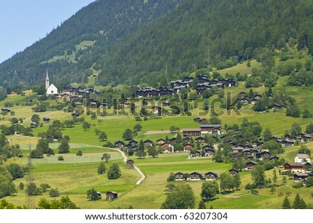 picturesque walser village with little church and traditional wooden houses with wide roofs in the swiss alps