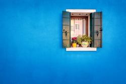 Picturesque window with blue house reflection on yellow wall of houses on the famous island Burano, Venice, Italy