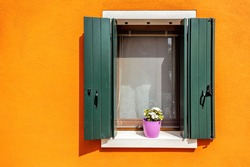 Picturesque windows with shutters and flowers on orange wall of houses on the famous island Burano, Venice, Italy