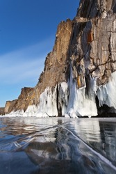 Picturesque winter landscape of frozen Baikal Lake on a sunny frosty day. Cliffs of Olkhon Island are reflected in the smooth surface of blue ice. Natural background. Ice travel and outdoor activities