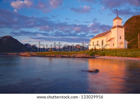 Picturesque wooden church on Lofoten islands in Norway lit by midnight sun