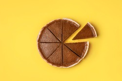 Pie slice separated from the whole pumpkin pie on yellow background. Minimal flat lay of autumn dessert. Traditional homemade American pie.