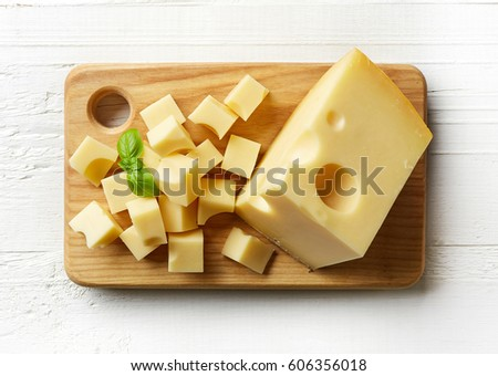 Piece and cubes of swiss cheese on cutting board. From top view