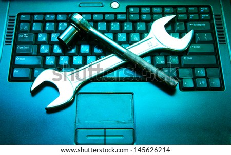 Piece blue and black laptop with a spanner on the keyboard