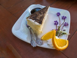 Piece homemade cake with cream, violet flower and slice orange decoration on white plate.