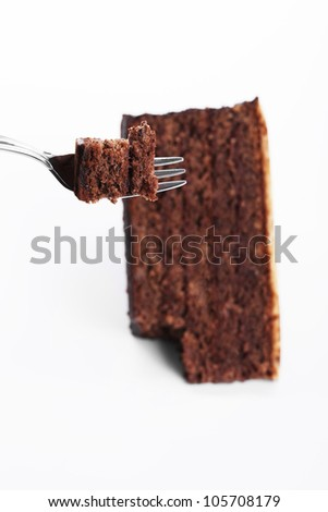 piece of a chocolate cake on a fork over a chocolate cake on white background