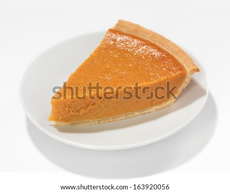 Piece of a pumpkin pie on a saucer isolated on white background