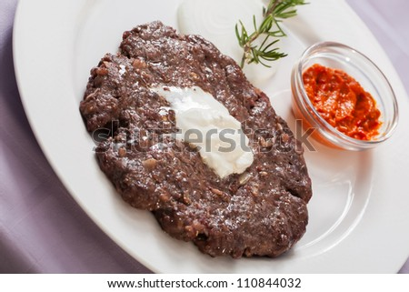 Piece of beef is served on a plate with chilly sauce.