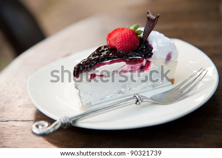 Piece of Blueberry Cheesecake topping with fresh strawberries on white plate closeup