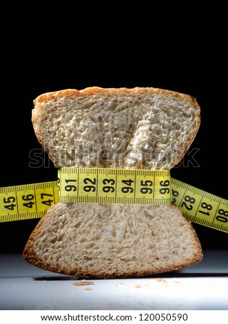 Piece of bread grasped by measuring tape with dark background