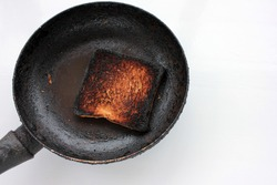 Piece of burnt toast bread on a plate on a white background. Top view, copy space