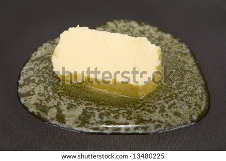 Piece of butter melting on non-stick frying pan