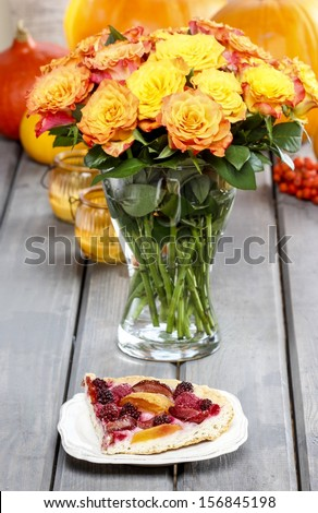 Piece of cake and huge bouquet of orange roses on wooden table. Ripe pumpkins and rowan berry in the background. Autumn party decor.