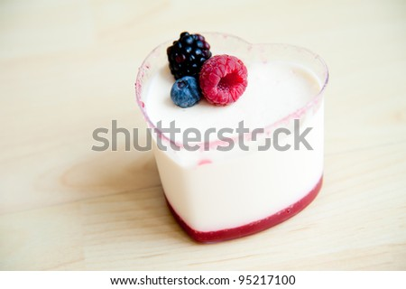 Piece of cake on wood pattern background : Panna Cotta in heart shape cup