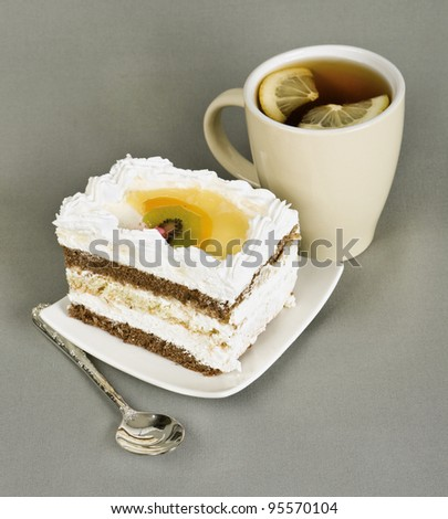 piece of cake with fruit, tea with a lemon, tea-spoon on grey fabric
