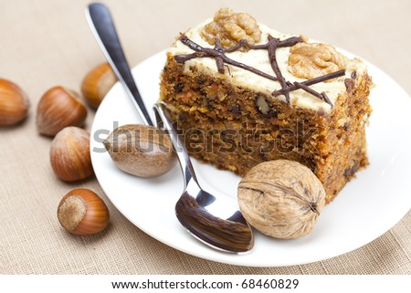 Piece of cake with nuts and spoon lying on a plate