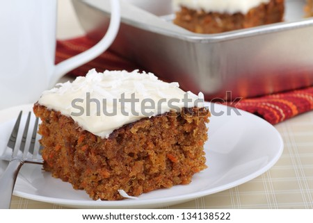 Piece of carrot cake with white icing and coconut